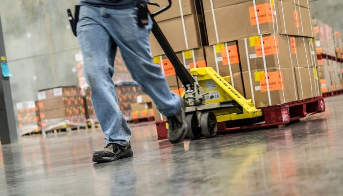 Employee pulling boxes in warehouse